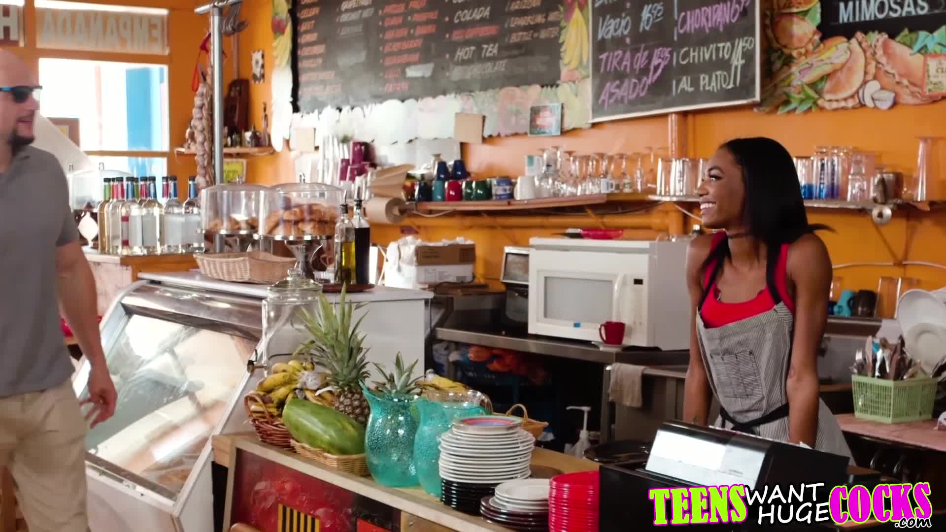 Gorgeous teen waitress gives her customer some hot chocolate